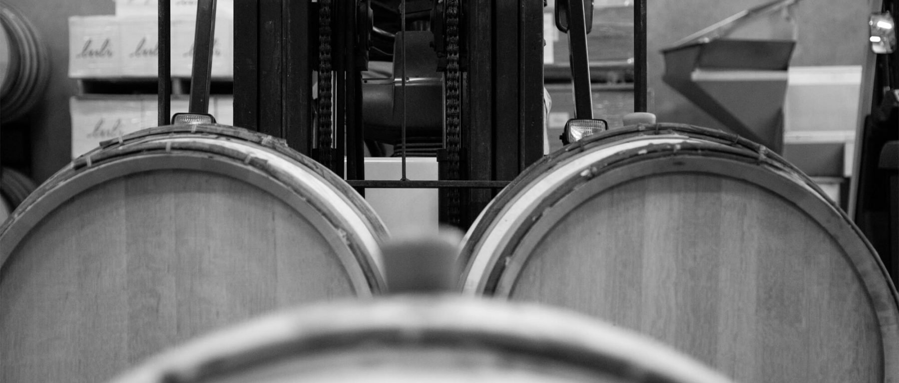 A certified Gravity Wine House employee uses a forklift to move wine barrels around the facility.